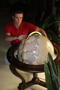 Justing Fisch examining a globe